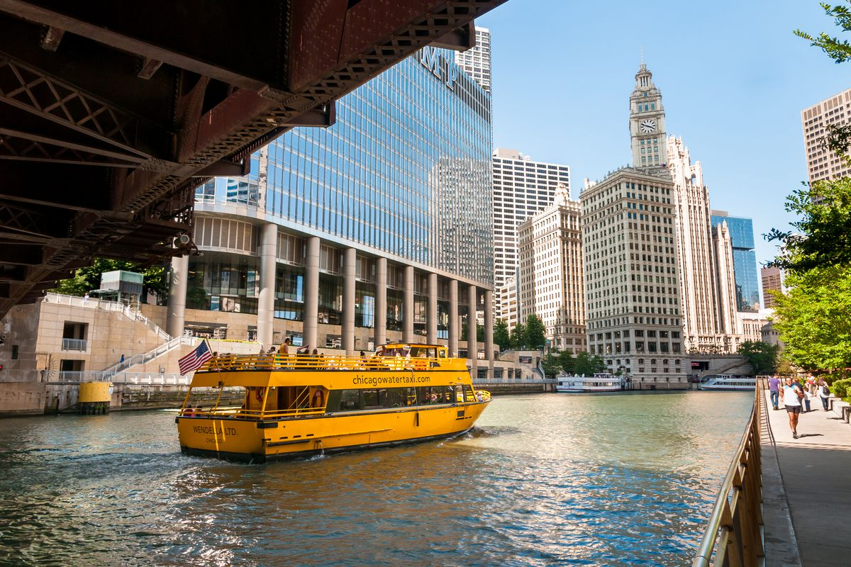 A bright yellow, two-deck boat passes below a bridge on an urban river. A glassy blue skyscraper is visible on the far bank and a pedestrian filled riverwalk on the near side.