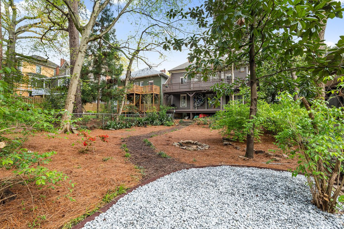 A backyard with trees and a gravel parking space.
