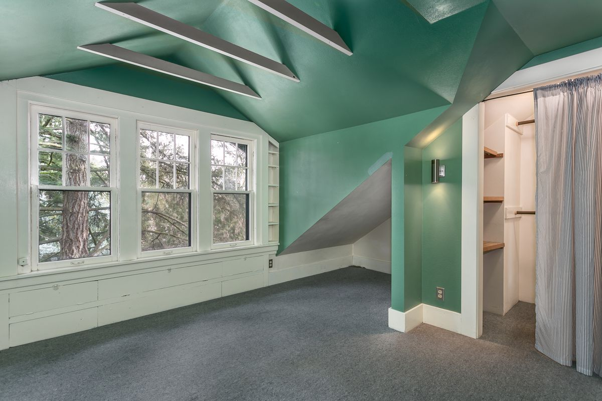 A finished attic room with vaulted ceilings, mint walls, and a little triangular nook in the corner.