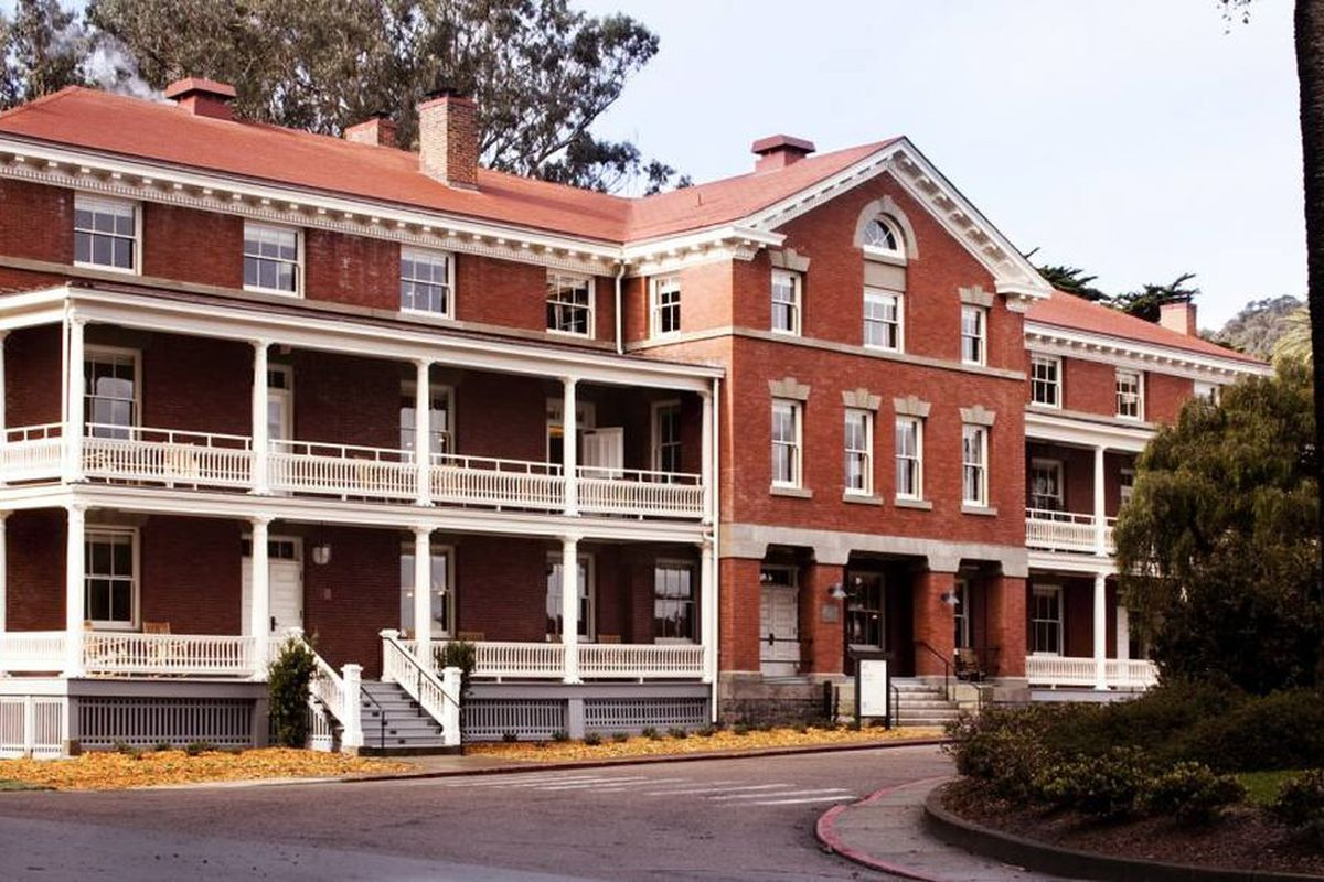 The exterior of the Inn at the Presidio in San Francisco. The facade is red with a white porch on two levels.