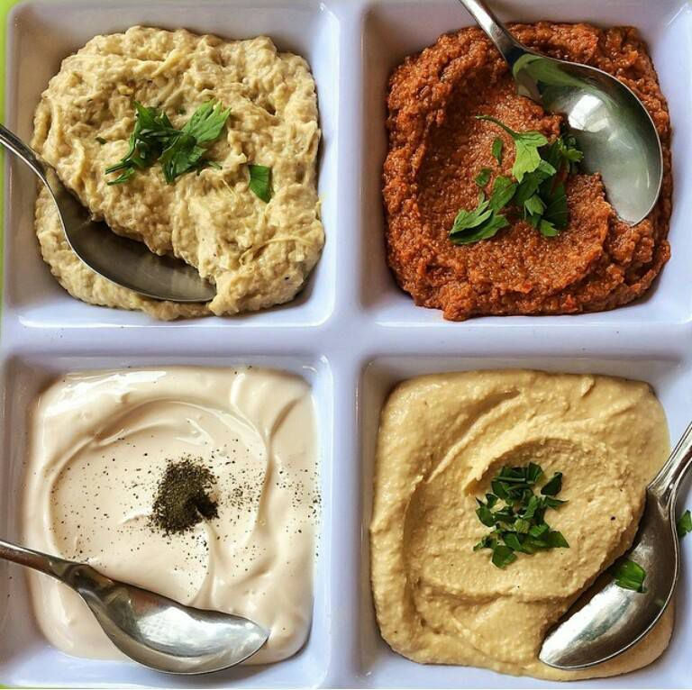 As seen from above, a segmented plate with four dips, each topped with a different herbal or spicy garnish