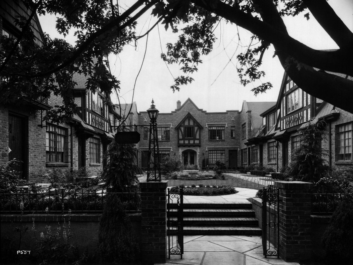 An apartment building with multiple half-timbered gables surrounds a large courtyard, with a brick wall and iron gate out front.