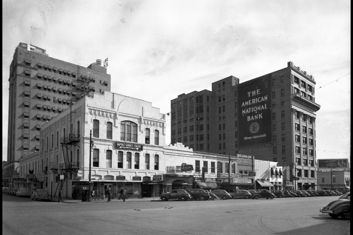 period black and white photo of buildings and cars in front