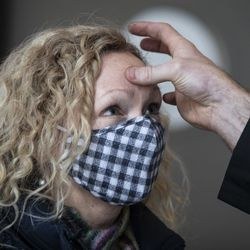 Janelle Peterson, 48, of the South Loop, receives the imposition of ashes from Pastor Ben Adams at Holy Trinity Lutheran Church in the South Loop on Ash Wednesday, Feb. 17, 2021.