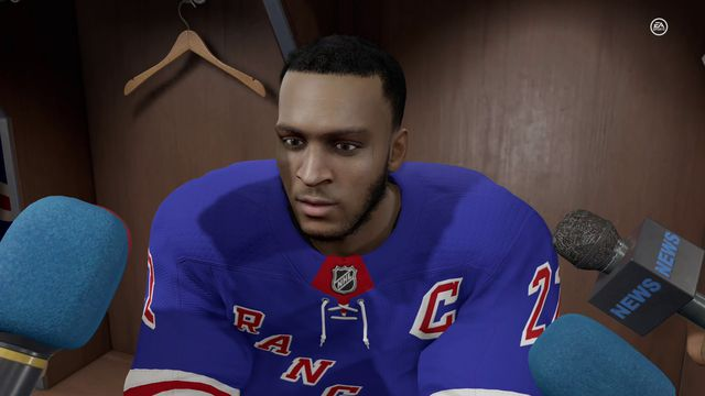 a brown-skinned New York Rangers player sitting at his locker for a media scrum in NHL 21's Be a Pro mode
