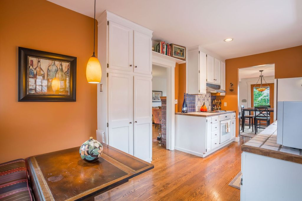 A breakfast nook in an orange-walled kitchen