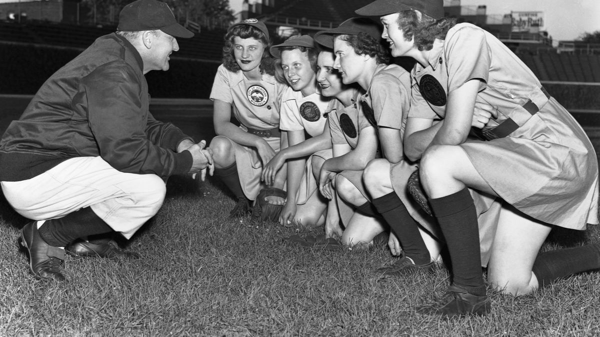 b5862207 Former hockey player Eddie Stumpf manages the Rockford Peaches of the  All-American Girls Professional Baseball League. Five of his players crouch  in front ...