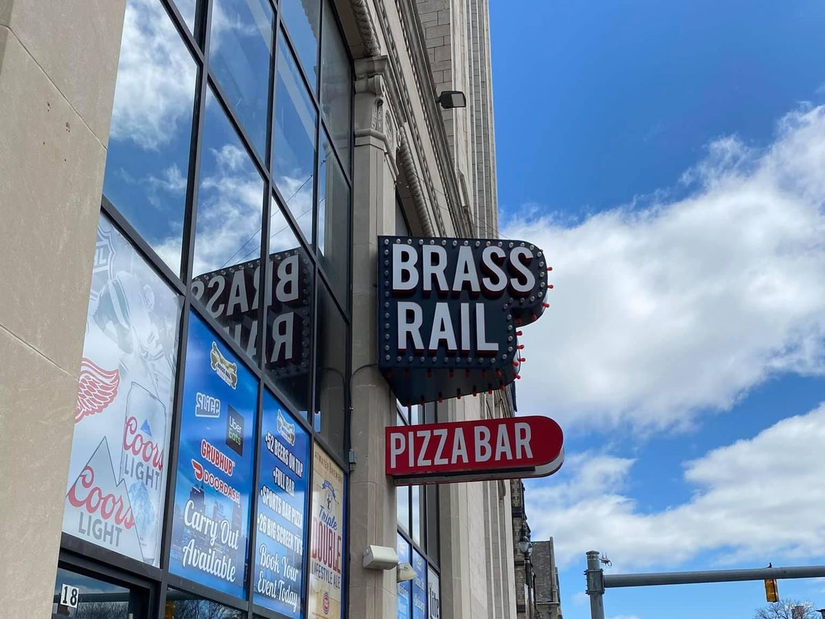 two signs that say brass rail pizza bar in red and white with a blue sky reflected in the windows