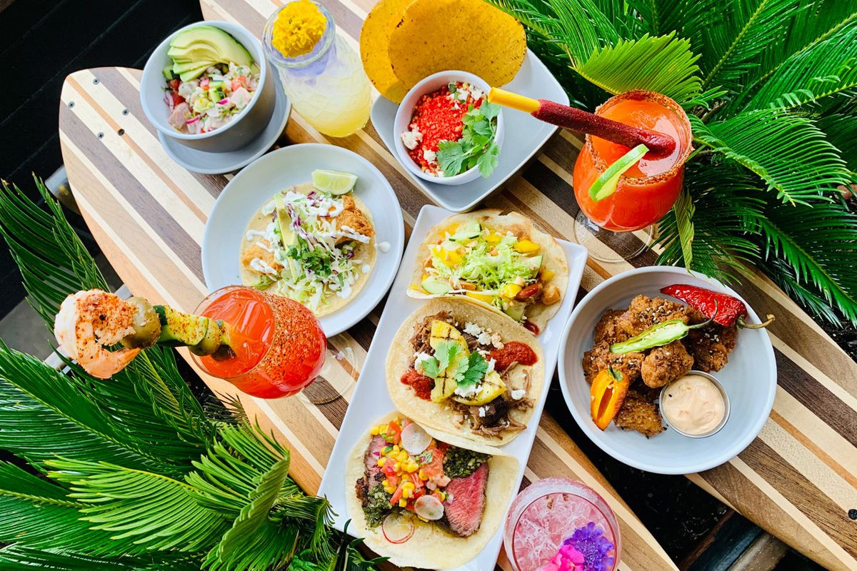 a spread of tropical-inspired food and drinks surrounded by palm fronts