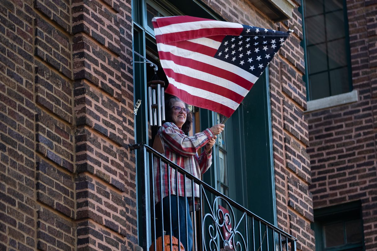 A woman with a flag on the balcony of an apartment.
