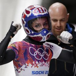 Noelle Pikus-Pace of the United States pumps her fists after her third run during the women's skeleton competition at the 2014 Winter Olympics, Friday, Feb. 14, 2014, in Krasnaya Polyana, Russia.