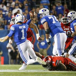 Brigham Young Cougar quarterback Zach Wilson (1) sacks off Utah defensive end Utes Bradley Ana (6) during the first half of an NCAA football game at LaVell Edwards Stadium in Provo on Thursday, August 29, 2019. .