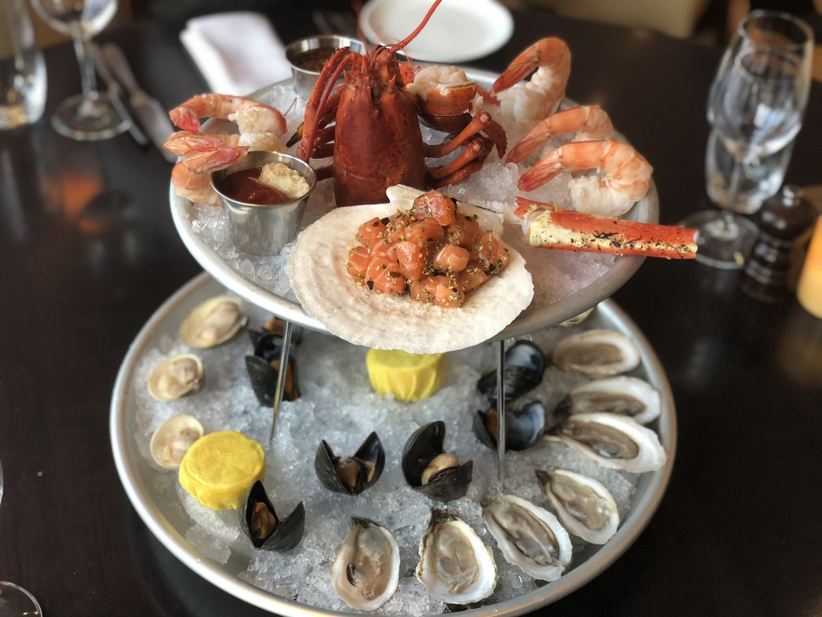 A two-tiered tower of seafood, including shrimp, oysters, lobster, and more