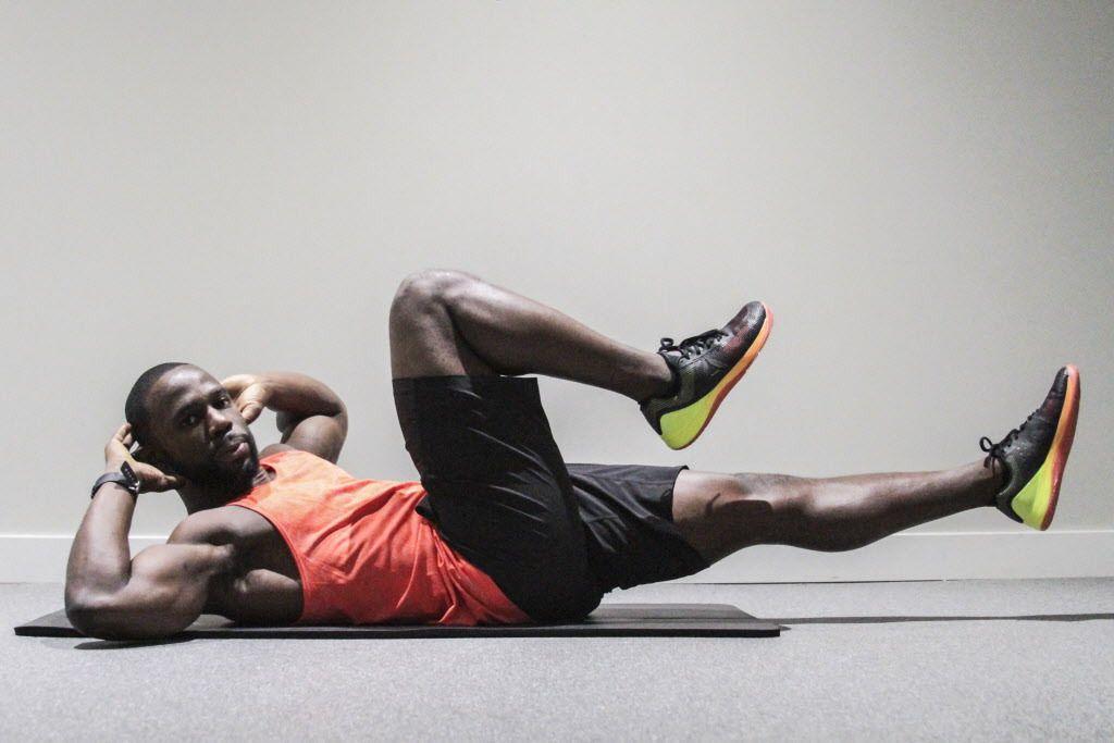Gideon Akande executes a bicycle crunch, an ideal exercise to fully work the abs.   Maria Cardona/ Sun-Times