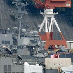 Damaged USS Fitzgerald is seen at Yokosuka Naval Base, south of Tokyo, Sunday, June 18, 2017.  Navy divers found the bodies of missing sailors Sunday aboard the stricken USS Fitzgerald that collided with a container ship Saturday in the busy sea off Japan, the Navy said.  (Kyodo News via AP)