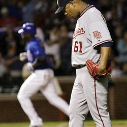 Washington Nationals starting pitcher Livan Hernandez, right, reacts after giving up a two-run home run to Chicago Cubs' Milton Bradley, left.