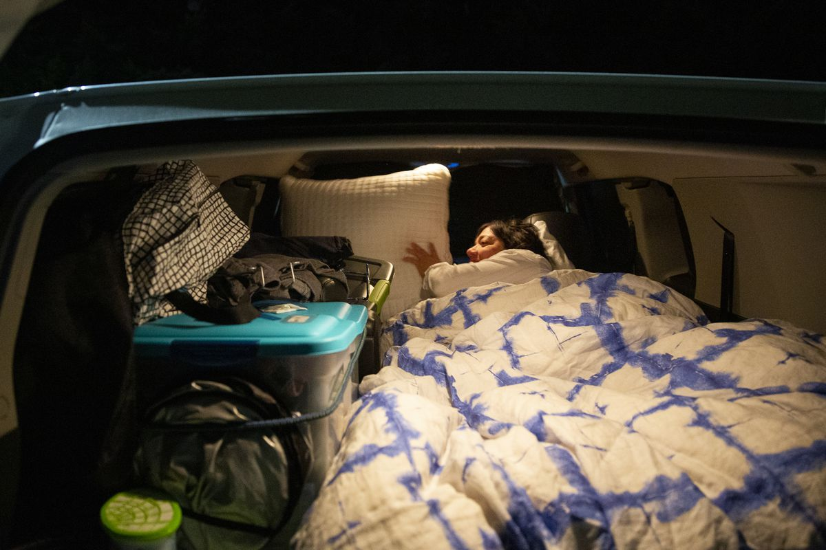 """Micki Denis prepares the bed in the car she lives in at Lake Washington United Methodist Church's parking lot in Kirkland, Wash., on Sunday, Oct. 13, 2019. Denis, who recently moved to the area, says she has a part-time job and doesn't make enough money to afford most apartment rents in the area. """"They don't offer full-time jobs to 65-year-olds,"""" she says. She hopes to return to travel in Europe, where she says she can live off her pension and Social Security. The church's Safe Parking program, started in 2011, helps women and families who are living in their vehicles by providing a 24-hour place to park, as well as access to a kitchen, bathrooms and Wi-Fi at night."""
