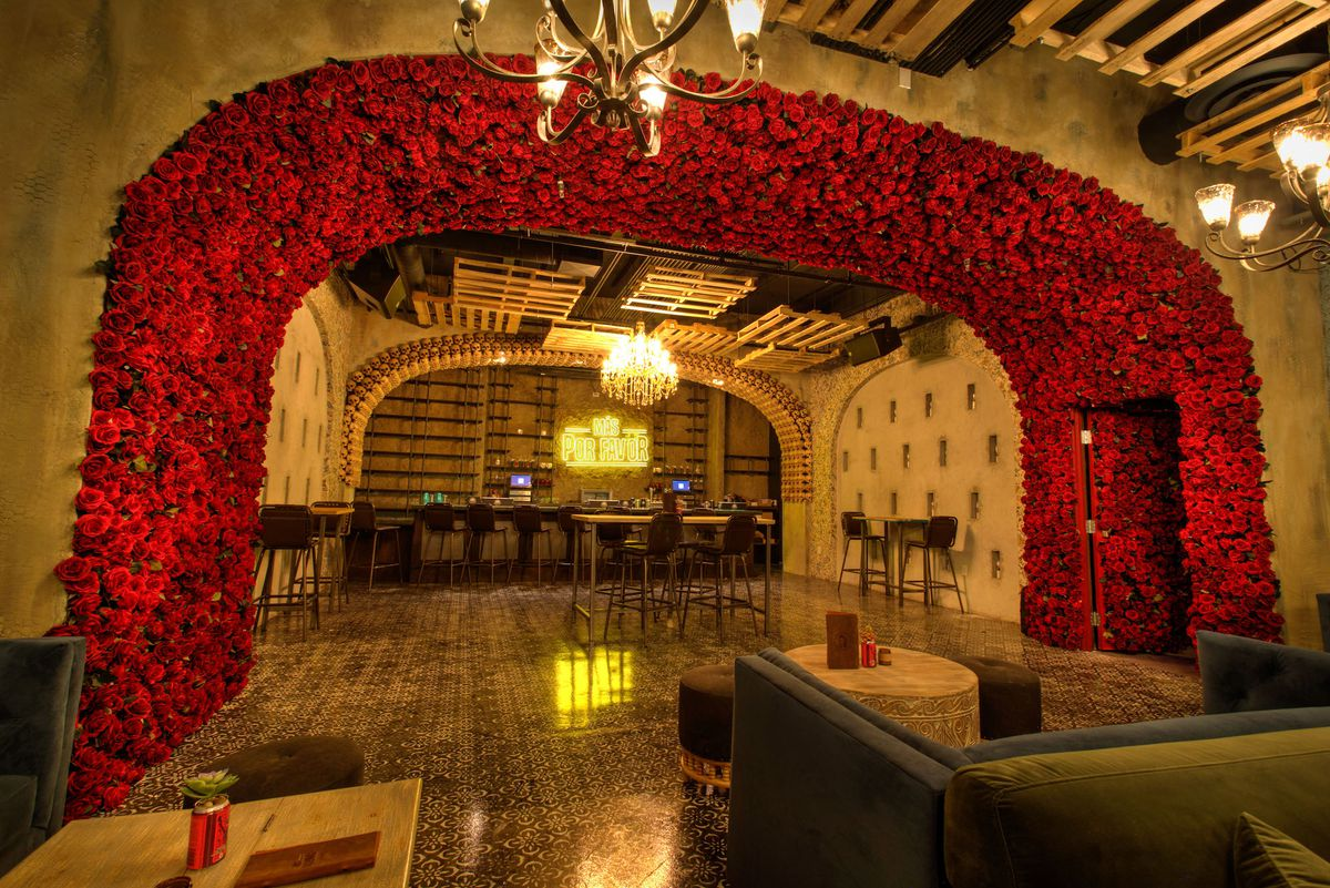 A rose arch separates the parlor from the bar at Más Por Favor Taqueria y Tequila