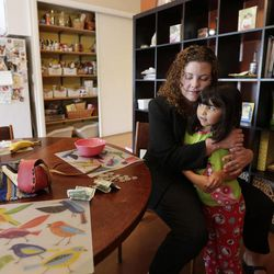In this Sept. 26, 2012 picture, Sabina Widmann hugs her daughter Luna at their home before going to work in San Diego.