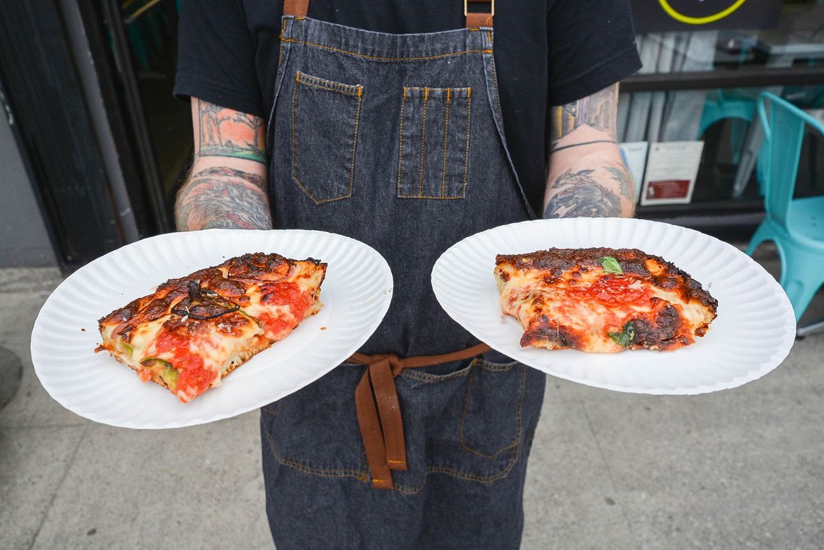 Hands hold two slices of pizza on paper plates outside.