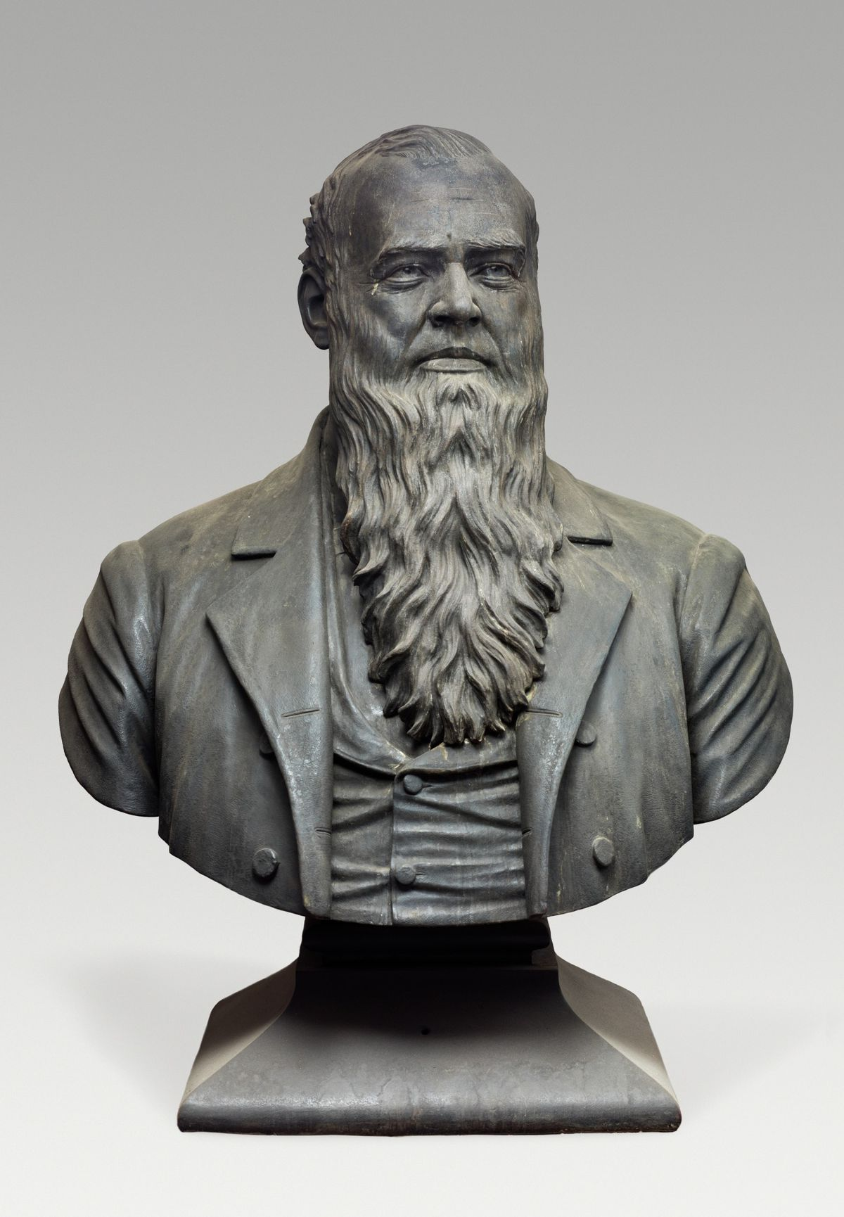 A bronze bust of the torso and head of a long-bearded, bald man in a three-piece suit.