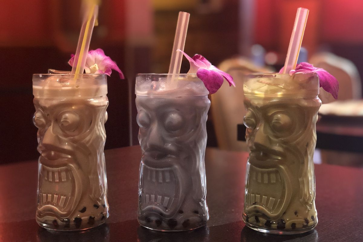 A row of three clear glass Tiki mugs with boozy boba cocktails in three colors. Each mug is garnished with an orchid and colored straw.