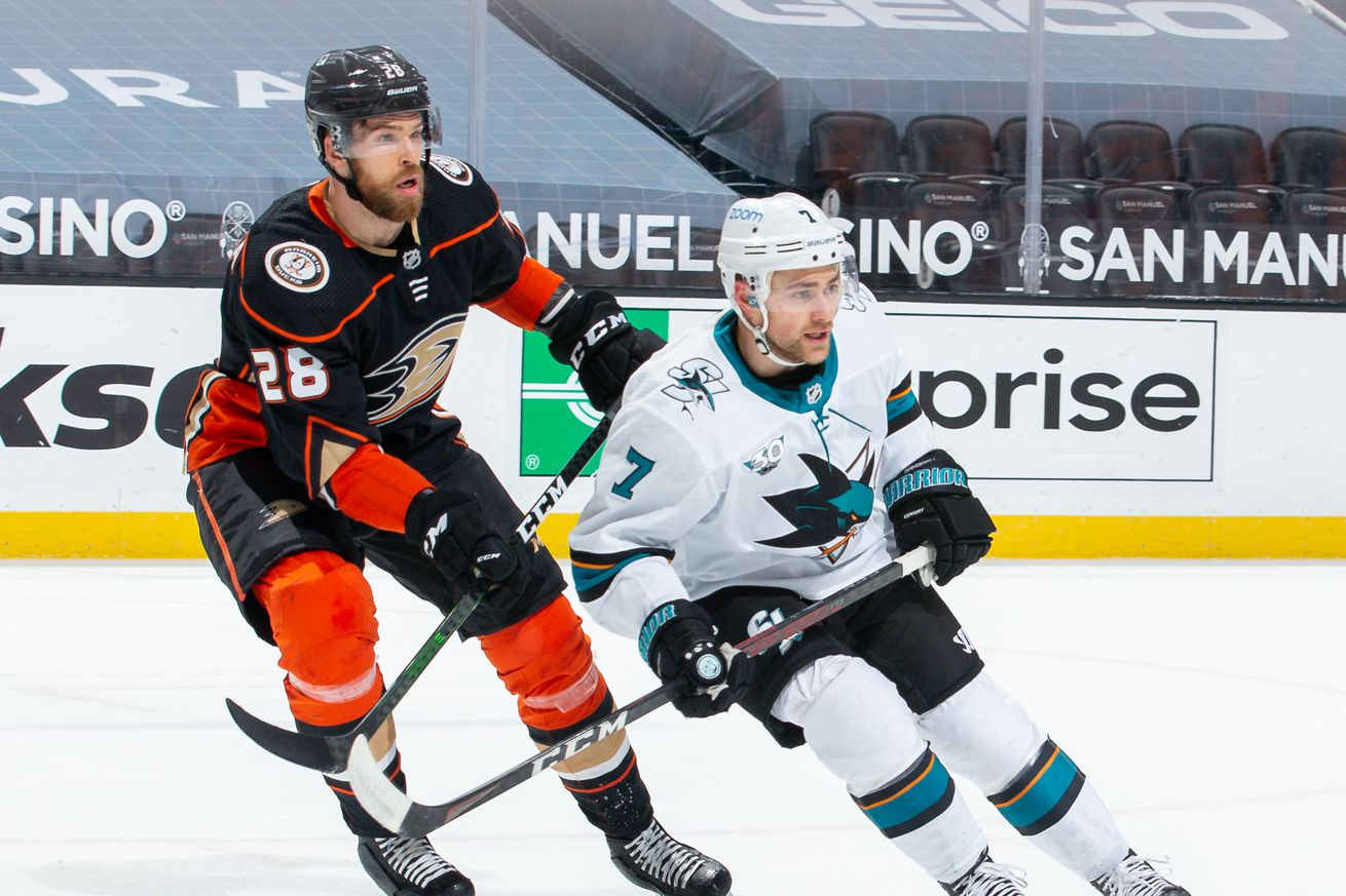 Jani Hakanpaa #28 of the Anaheim Ducks and Dylan Gambrell #7 of the San Jose Sharks skate against each other during the first period of the game at Honda Center on March 13, 2021 in Anaheim, California.
