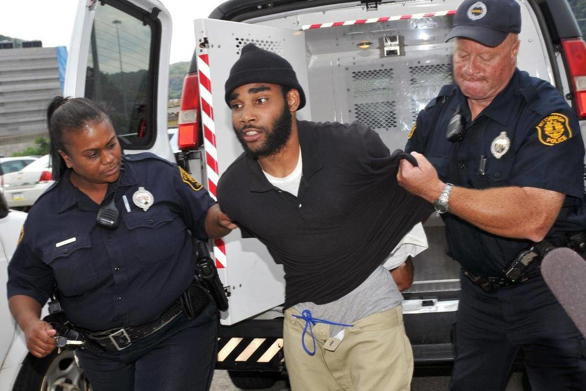 FILE - In this Sept. 21, 2012 photo, Klein Michael Thaxton, center, is lead into Pittsburgh Police headquarters after being apprehended without incident at Three Gateway Center in Pittsburgh, where held a businessman hostage inside the office building for