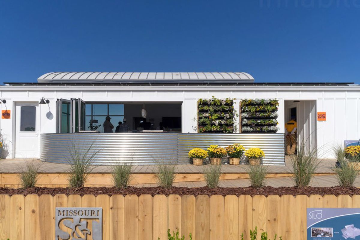 A white, low, flat-roofed home with open sides and a green wall with a corrugated metal enclosure.