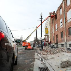A worker checks the brick facade of a building at 500 South and 400 West in Salt Lake City afte a 5.7 magnitude earthquake centered in Magna on Wednesday, March 18, 2020.
