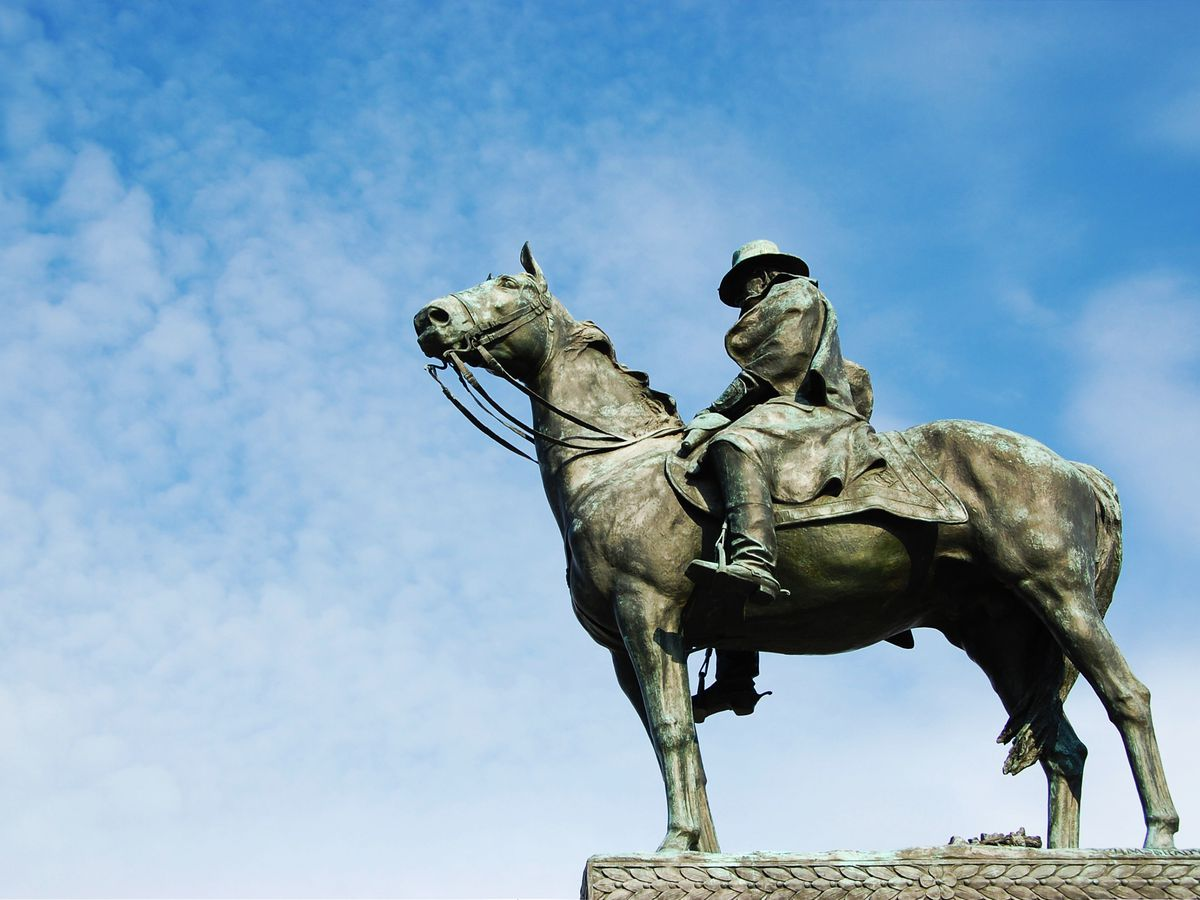 A statue of Ulysses S. Grant riding a horse beneath blue skies.