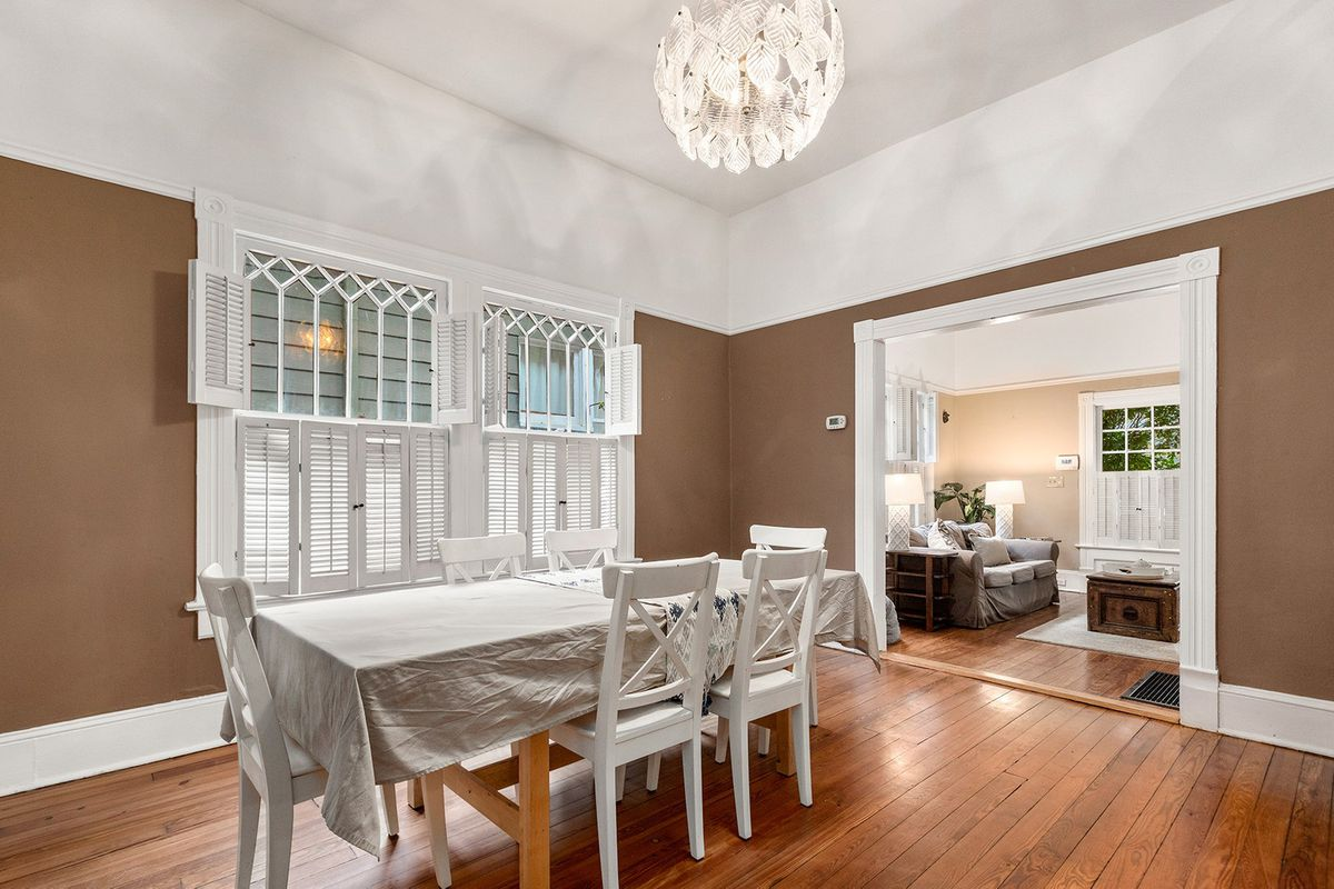 A dining room with ancient wood floors and a newer chandelier overhead.