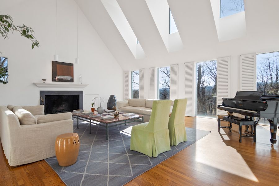 A living room with large windows, dormer windows, a fireplace, and seating and a piano.