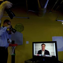 Members of the media take photographs and record sound from a monitor showing Republican presidential candidate, and former Massachusetts Governor Mitt Romney as he participates in a live-streaming internet discussion at the Chicago Headquarters of Google, in Chicago, Tuesday, March 20, 2012. (AP Photo/Steven Senne)