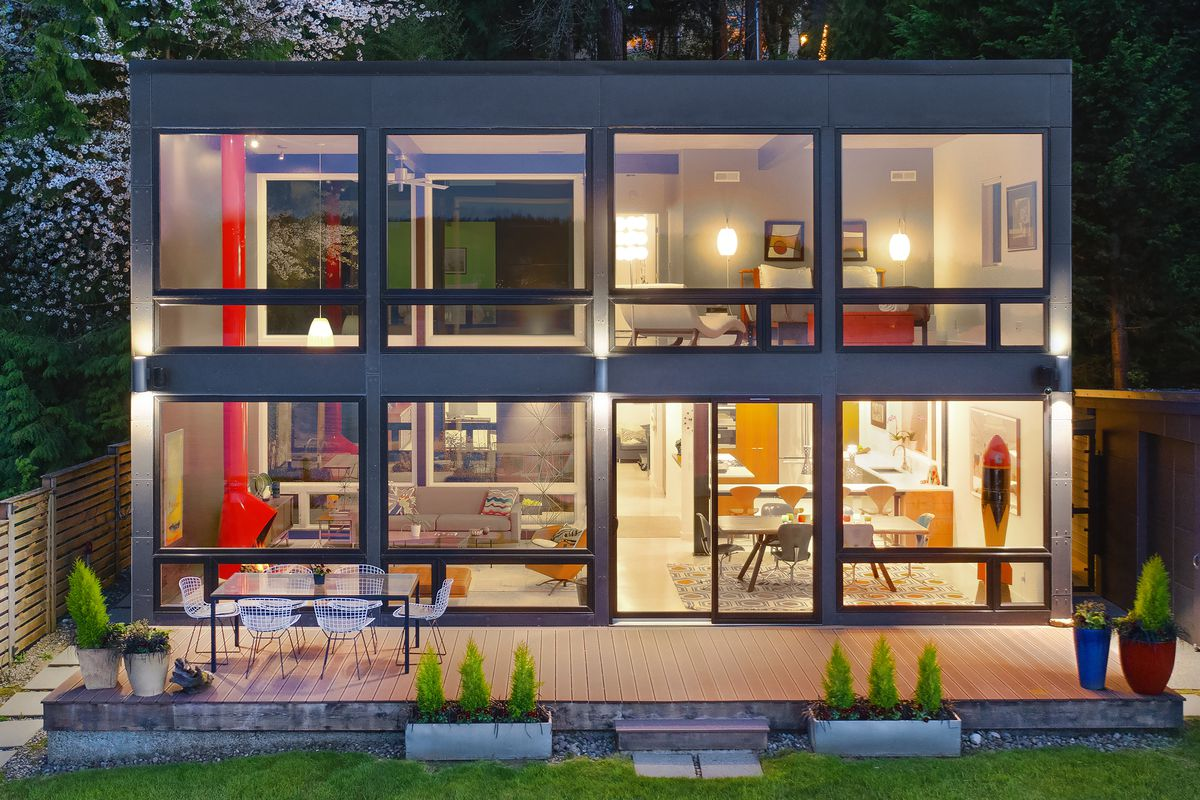 An exterior view of a boxy glass house at dusk. The lights are on inside the house so you can seethe living room and a kitchen.