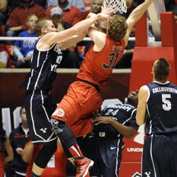 Brigham Young Cougars forward Eric Mika (00) commits a flagrant foul on Utah Utes center Dallin Bachynski (31) during a game at the Jon M. Huntsman Center on Saturday, Dec. 14, 2013.