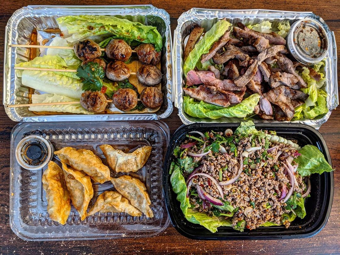 Overhead view of four takeout containers of Thai food, including fried meatballs on skewers, fried dumplings, a ground pork salad, and more