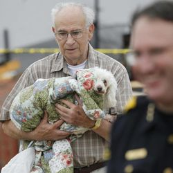 """David Lowe carries his daughter's dog """"Phoebe"""" after it was rescued by officials who found it under a destroyed home, Tuesday, April 3, 2012 after a storm moved through Arlington, Texas. Tornadoes tore through the Dallas area Tuesday, peeling roofs off homes, tossing big-rig trucks into the air and leaving flattened tractor trailers strewn along highways and parking lots."""