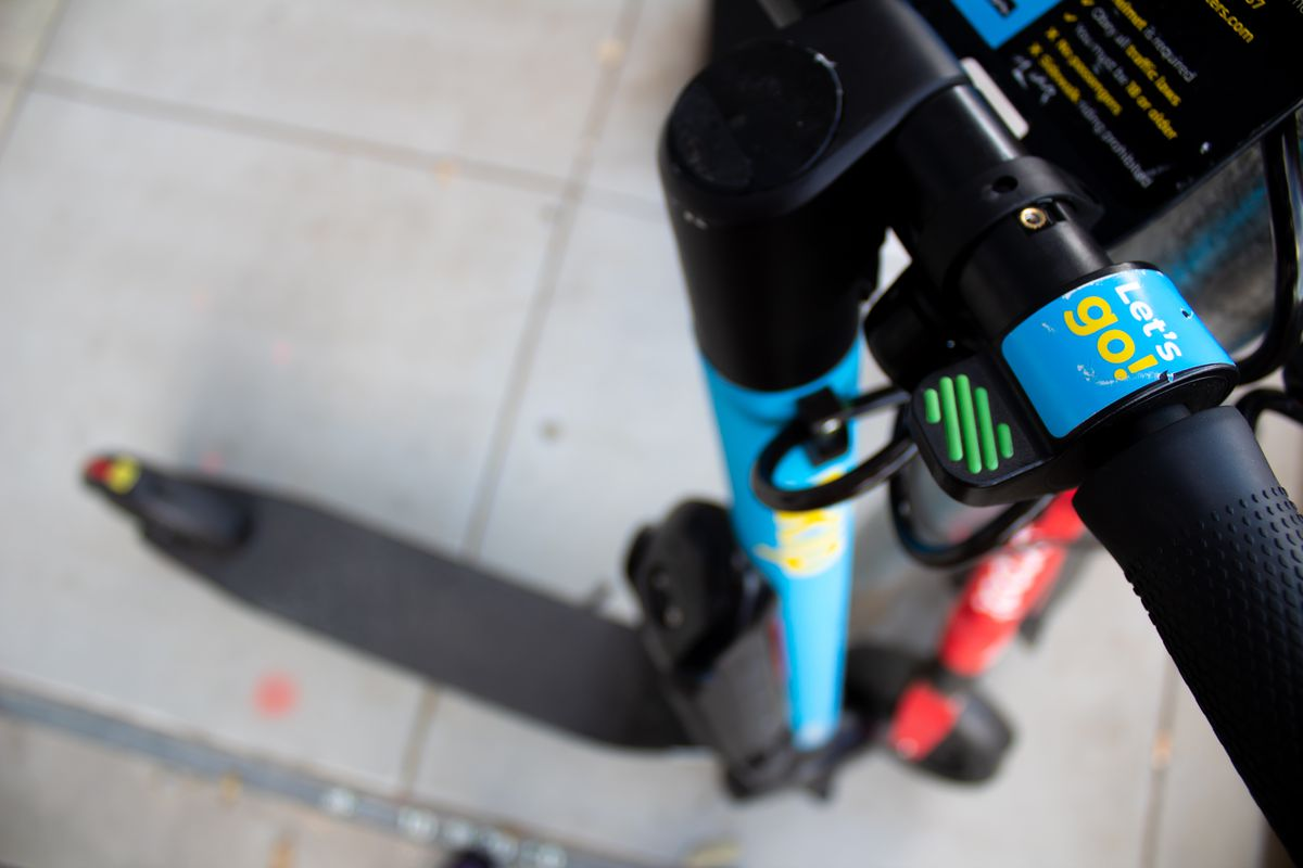 """Close-up of e-scooter handle light blue with yellow lettering that says """"Let's Go!"""""""
