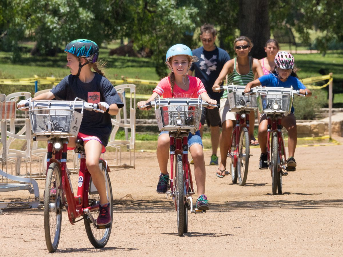 Kids and adults on similar bikes with baskets on a crushed granite trail. The bikes are part of Austin's B-cycle rental program.