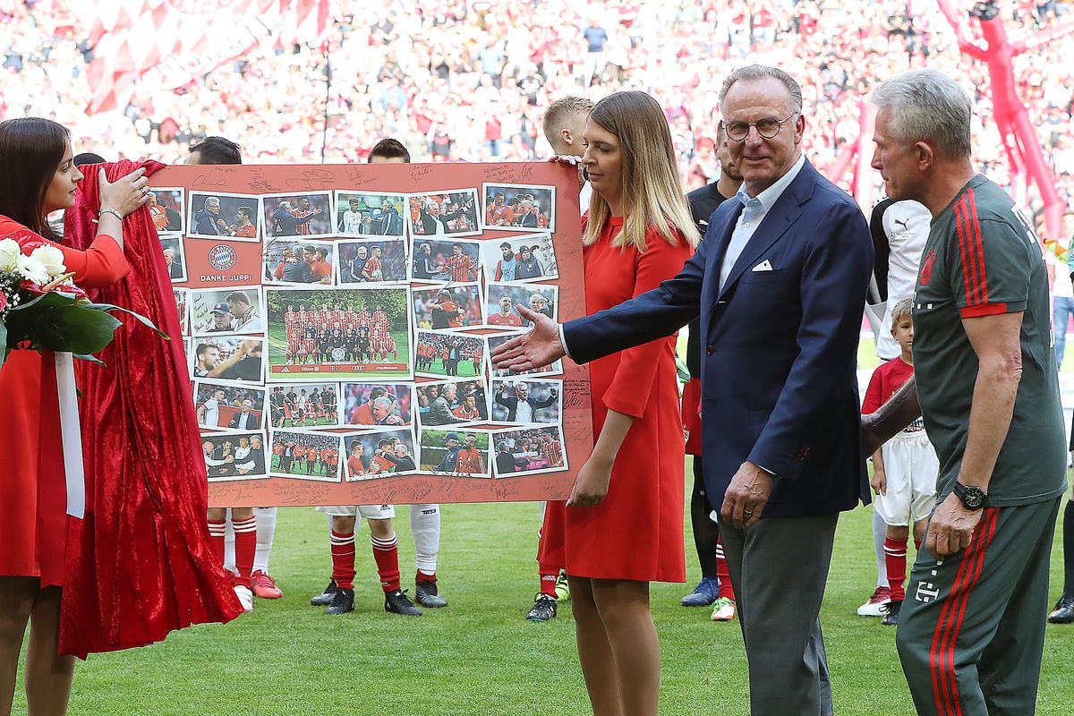 MUNICH, GERMANY - MAY 12: Jupp Heynckes, head coach of Bayern Muechen, (r) is presented with a present by Karl-Heinz Rummenigge of Muenchen (2nd right), as Uli Hoeness L) looks on, during his farewell ceremony during the Bundesliga match between FC Bayern Muenchen and VfB Stuttgart at Allianz Arena on May 12, 2018 in Munich, Germany.
