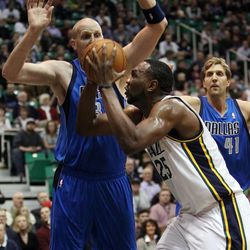 Al Jefferson of the Utah Jazz takes a shot while defended by Chris Kaman of the Dallas Mavericks during NBA basketball in Salt Lake City, Monday, Jan. 7, 2013. At right is Dirk Nowitzki of the Dallas Mavericks.