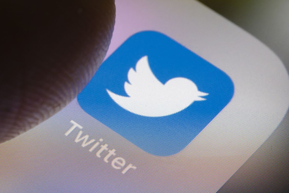A finger hovers above a Twitter app icon on a smartphone screen.