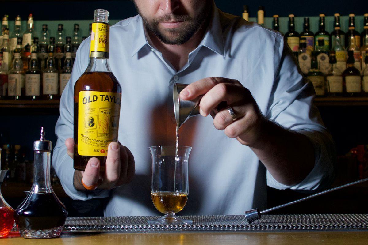 A man pours liquor into a glass