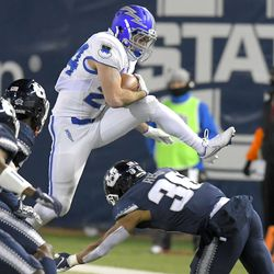 Air Force running back Kadin Remsberg (24) leaps over Utah State safety Jared Reed (36) during the second half of an NCAA college football game Thursday, Dec. 3, 2020, in Logan, Utah.