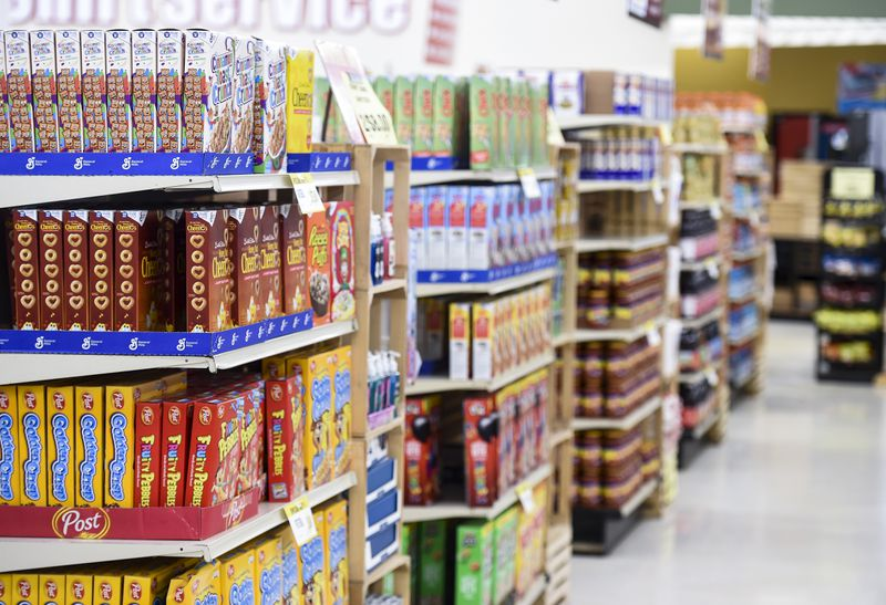 A grocery store aisle with fully stocked shelves of cereal and other packaged goods.