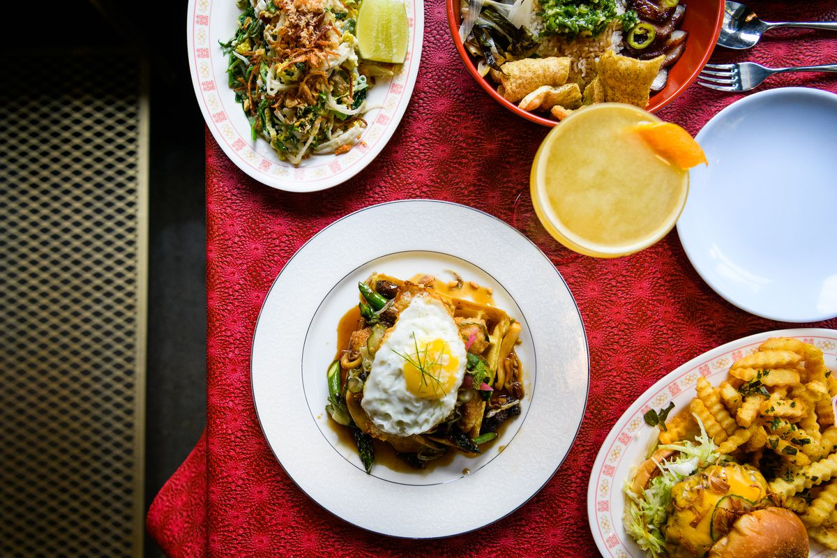 On a red tablecloth, a pile of sweetbreads topped with an egg, a stir-fry of vegetables, a burger, and a cocktail all sit at Oma's Hideaway