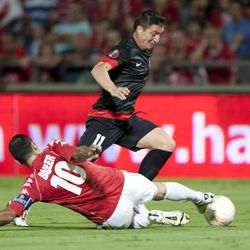 Atletico Madrid's Cristian RodrÍguez, right, goes past Hapoel Tel Aviv's Walid Badier during their Europa League Group B soccer match at the Bloomfield stadium in Tel Aviv, Israel,Thursday, Sept. 20, 2012.