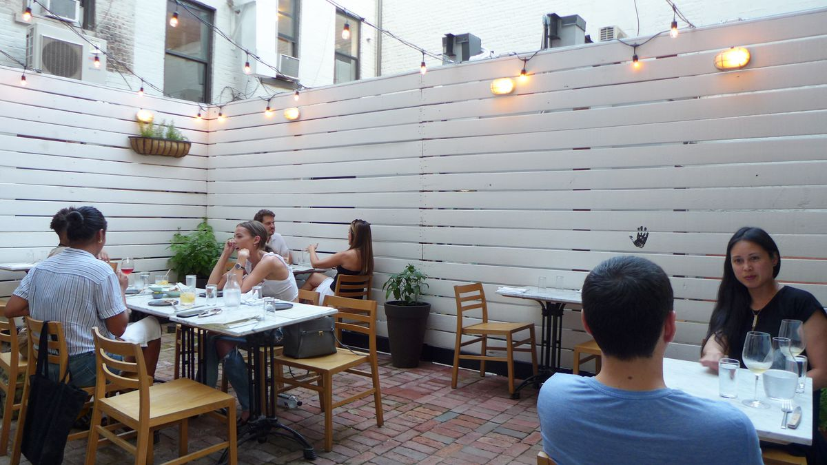 Several tables of diners sitting in a fenced in back yard behind a restaurant.