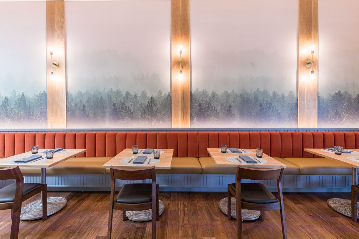 Two-person tables against a wall with orange tufted banquettes. A mural of grey, green, and blue trees covers the wall.